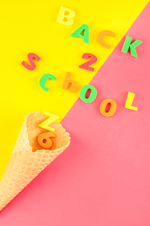 Creative flat lay back to school concept with waffle cone and welcome letters message on bright yellow and pink paper background with copy space, template for text or design