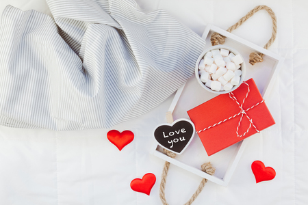 Photo for Creative Top view flat lay sill life romantic composition. Hot cacao coffee chocolate with marshmallows mug red gift hearts tray in bed. Concept Valentine holiday cozy warm home morning natural light - Royalty Free Image