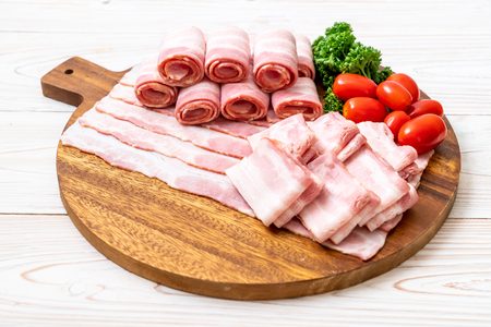 sliced raw pork bacon on wood board