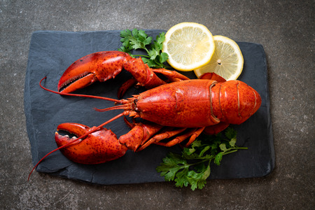Photo pour red lobster with vegetable and lemon on black slate plate - image libre de droit