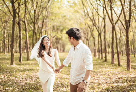 Photo pour Happy Asian couple in love with tree arch at park - image libre de droit