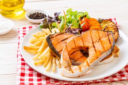 Foto de double grilled salmon steak fillet with vegetable and french fries - Imagen libre de derechos