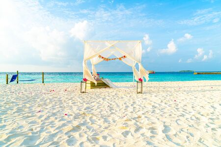 Foto de wedding arch on beach with tropical Maldives resort and sea background - vintage effect filter - Imagen libre de derechos