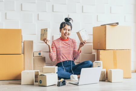 Photo pour Asian Women business owner working at home with packing box on workplace - online shopping SME entrepreneur or online selling concept - image libre de droit