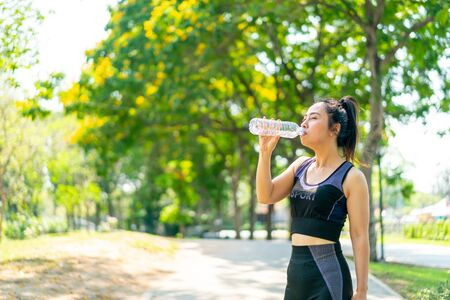 Photo pour Asian woman drinking water in sportwear after exercise at park - image libre de droit