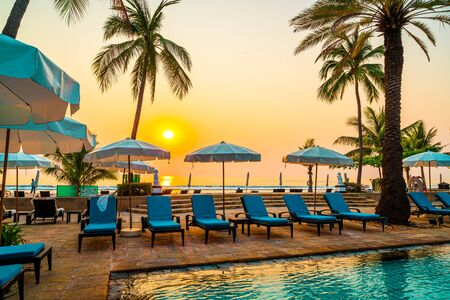 Photo for Beautiful palm tree with umbrella chair pool in luxury hotel resort at sunrise times - Royalty Free Image