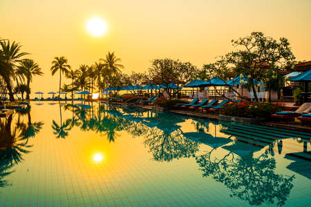 Photo for beautiful palm tree with umbrella chair pool in luxury hotel resort at sunrise times - holiday and vacation concept - Royalty Free Image