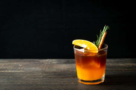 Photo pour A glass of iced americano black coffee and layer of orange and lemon juice decorated with rosemary and cinnamon - image libre de droit