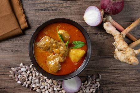 Photo pour Chicken massaman curry in black bowl with herb and spices on wooden background. Thai authentic food called massaman kai. top view. Flat lay. - image libre de droit