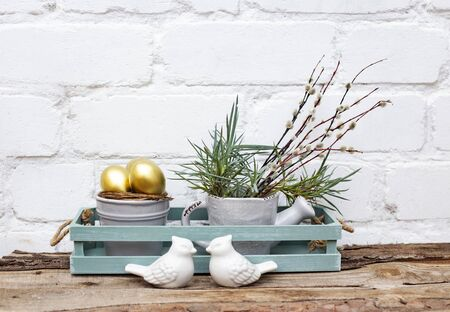 Photo pour Gold Easter eggs in ceramic grey busket and spring grass with willow in decorayive grey watering can in purist blue box on wooden table with brick wall background. Copy space Place for text - image libre de droit