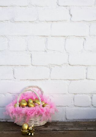 Photo pour Easter gold eggs in white wooden basket with pink feathers near gold rabbit on dark brown wood table near brick background. Vertical, copy space. - image libre de droit