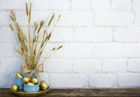 Photo pour Easter decoration with gold eggs in blue pots with dry dyed wheat spikes on wooden table near white brick background. Horizontal, copy space. Place for text - image libre de droit