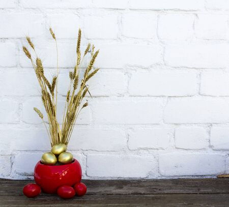 Photo pour Easter decoration with gold and red eggs in a pot with dry dyed wheat spikes on wooden table near white brick background. Copy space. Place for text. - image libre de droit