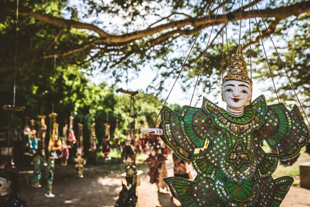 Myanmar traditional puppets hanging under a big tree for sale as a souvenir for tourist