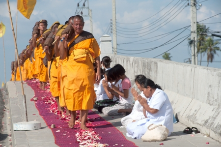 Bangkok,Thailand-January 21,2012   Row of Buddhist hike Thai monks on streets strewn with rose petals on the Thammachai hike establish the path of the great teachers on January 21,2012 in Bangkok , Thailand