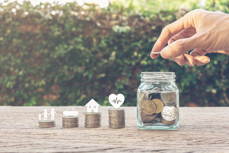Photo pour Savings money for family life concepts. Hand holding coin on a full money in glass jar and family member, car, house, healthy on coins. Depicts saving for wealth and life. fundraising concept. - image libre de droit