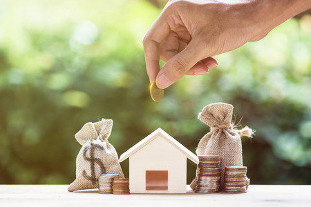 Photo pour Saving money, home loan, mortgage, a property investment for future concept. A man hand putting money coin over small residence house and money bag with nature background. A sustainable investment. - image libre de droit
