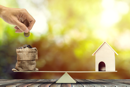 Photo pour Real estate investment, home loan, reverse mortgage, savings to buy home concepts. House wood model, Hand putting coin into a bags on wood balance scale. depicts a funding for real estate investment. - image libre de droit