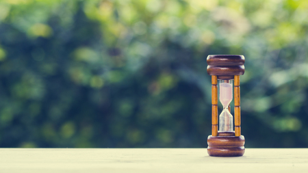 Photo pour The time concepts. Hourglass on wooden table with green nature background and space at the left. Business countdown to a deadline concepts. Depicts our time is steadily decreasing. Saving a times. - image libre de droit