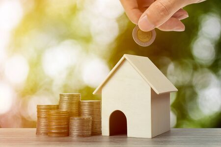 Photo pour a property investment for future concept. A businessman hand putting money coin over small residence house and stacked coins. Depicts a sustainable investment. - image libre de droit