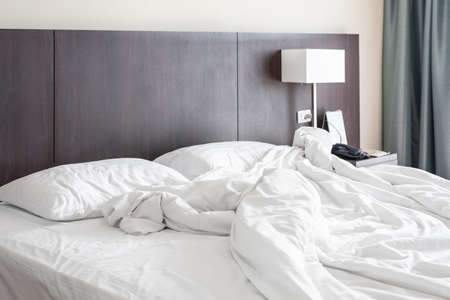 Photo pour Messy and unmade white hotel bed at hotel room in holiday morning. - image libre de droit