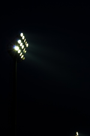 Stadium floodlights on a sports field at night
