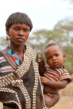 omo valley, ethiopian - august 10, 2011: women of ethnic tsemay with his son in the village, the omo valley ethnic groups could disappear with the construction of gibe iii hydroelectric dam.