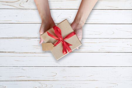 Woman hand holding gift box on wood plank and painted in white color with copy space.