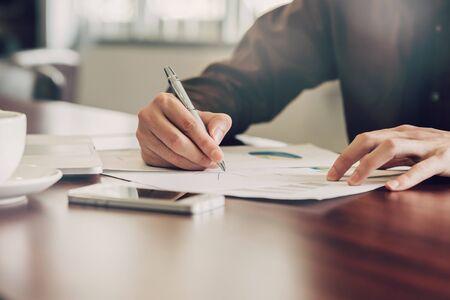 Photo pour business man hand writing note paper on wooden table - image libre de droit