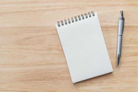 Photo pour Top view of blank notebook with pen and natural light on wooden table. - image libre de droit