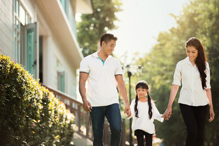 Photo pour Asian family are going out of the house. Parents and children were walking hand in hand together a happy - image libre de droit