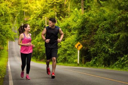 Foto de man and woman jogging in the forest - Imagen libre de derechos