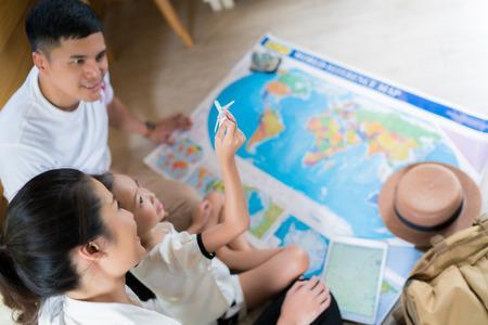 Foto de Asian family are planning to around the world. the image focus plane was carrying a child. - Imagen libre de derechos