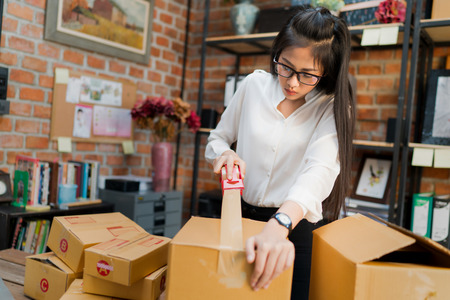 Photo pour Business woman are packing boxes to send to customers. - image libre de droit