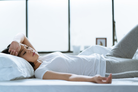 Asian girl is headache in bed.