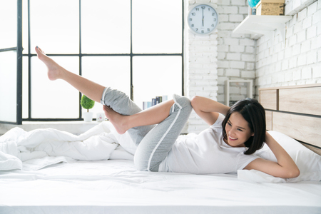Photo pour Asian women exercising in bed in the morning, she feels refreshed. - image libre de droit