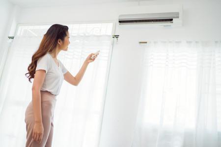 Photo pour Asian woman Holding Remote Control Air Conditioner In House - image libre de droit