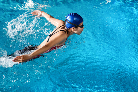 Photo pour Swimmers are swimming butterfly poolside at night. - image libre de droit