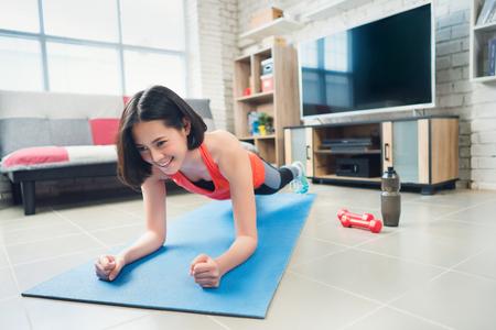 Foto de Asian woman she pretends plank on a yoga mat. She exercises at home. - Imagen libre de derechos