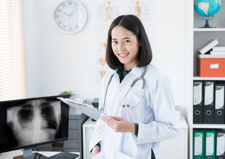 Photo pour The doctor is sitting in the room to see the patient. She is opening x-ray effects. - image libre de droit