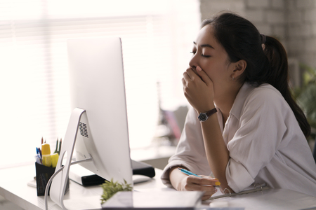 Photo for Businesswoman, yawned she was tired of working in an office. - Royalty Free Image