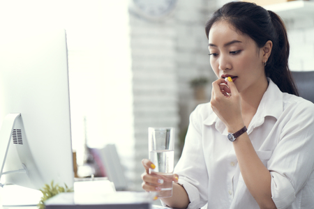 Photo pour Business woman drinking water and taking medicine. She feels like sick - image libre de droit