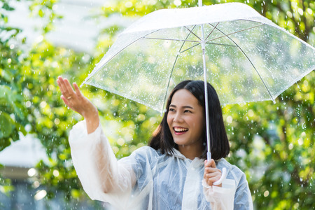 Photo for Rainy day asian woman wearing a raincoat outdoors. She is happy.She used her hand to touch the rain. - Royalty Free Image
