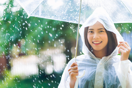 Photo pour Rainy day asian woman wearing a raincoat outdoors. She is happy. - image libre de droit