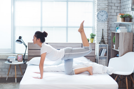 Photo pour Asian woman exercising in bed in the morning, she feels refreshed. - image libre de droit