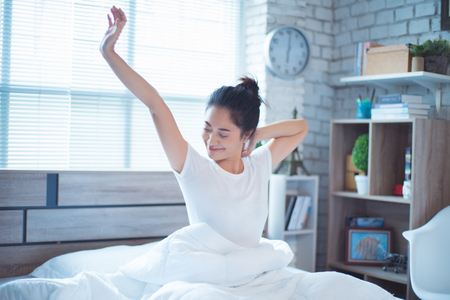 Photo for Asian woman exercising in bed in the morning, she feels refreshed. - Royalty Free Image