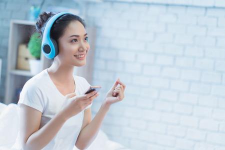 Foto de Asian woman  listening to music and  sings in the room happily - Imagen libre de derechos
