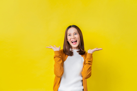 Foto de Asian girl is surprised. She is excited.Yellow background studio - Imagen libre de derechos