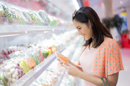 Foto de The woman is in the supermarket  shopping for food - Imagen libre de derechos