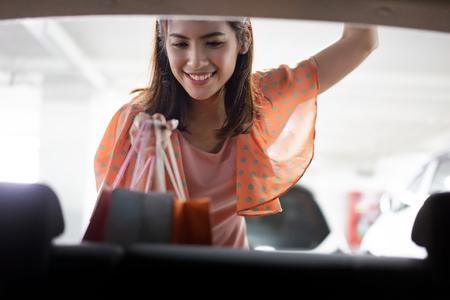 Photo pour Woman  putting the shopping bags into her car. - image libre de droit